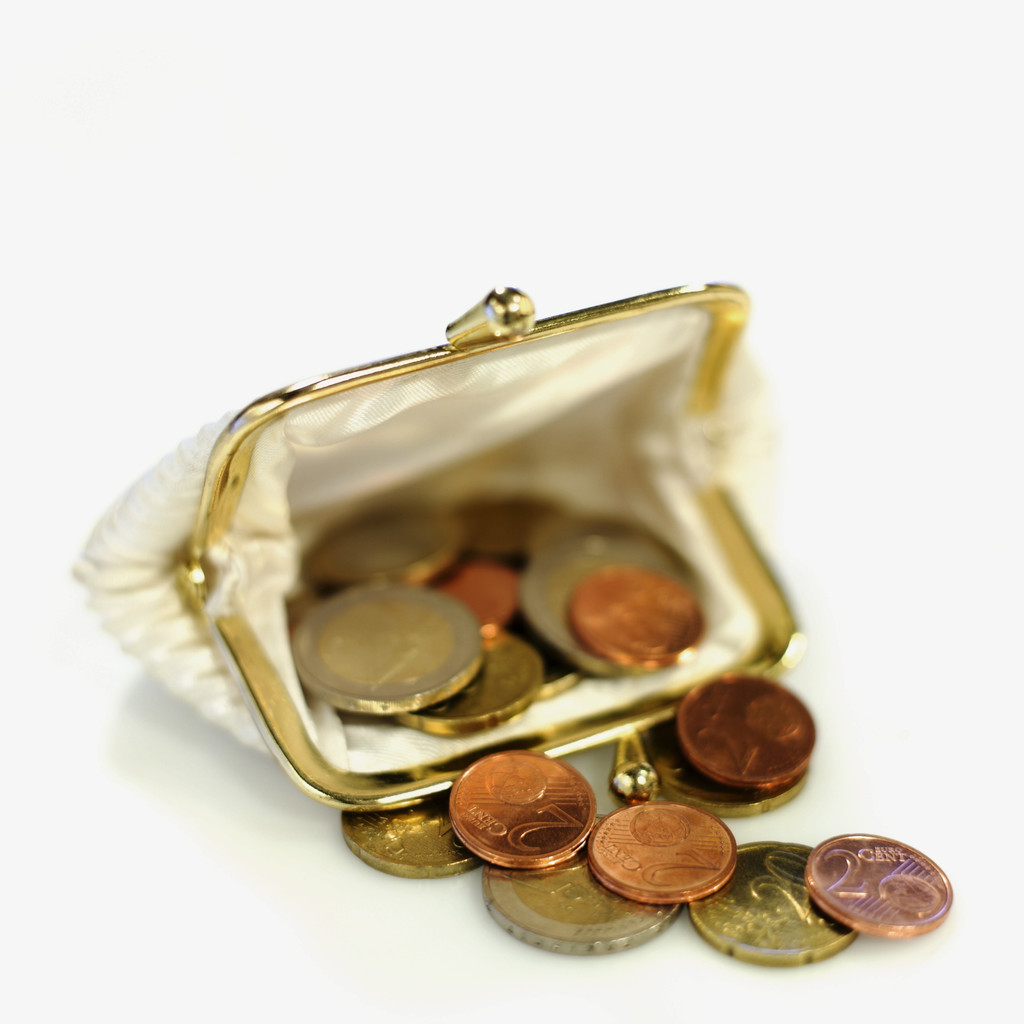 Close-up of euro coins spilling out of change purse --- Image by © Royalty-Free/Corbis